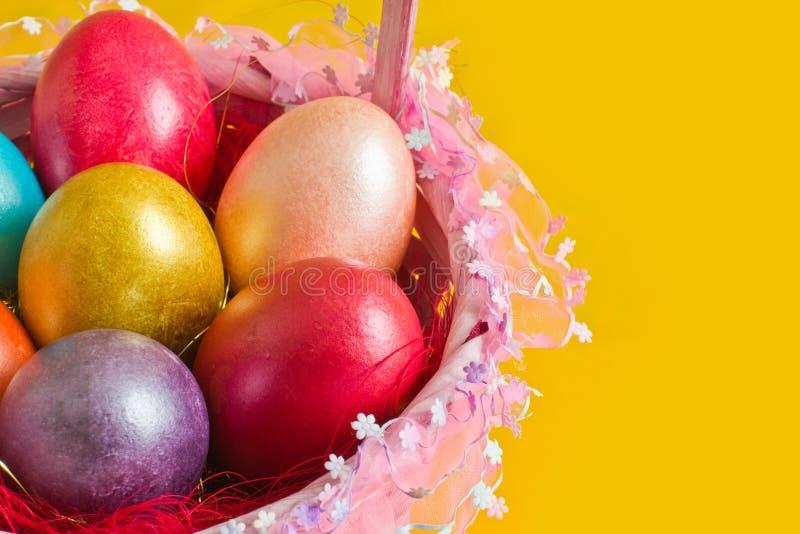 Корзина с цветастыми пасхальными яйцами стоковые изображения