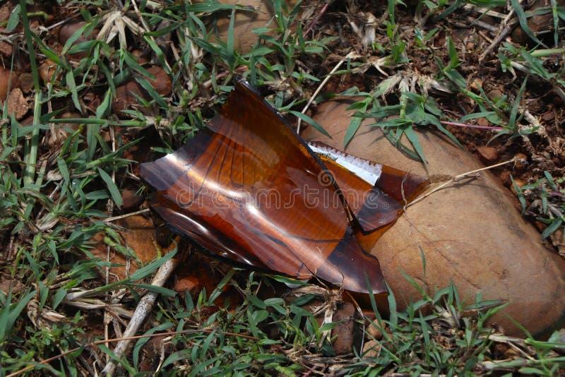 Коричневая стеклянная бутылка пива сломана на земле стоковое изображение