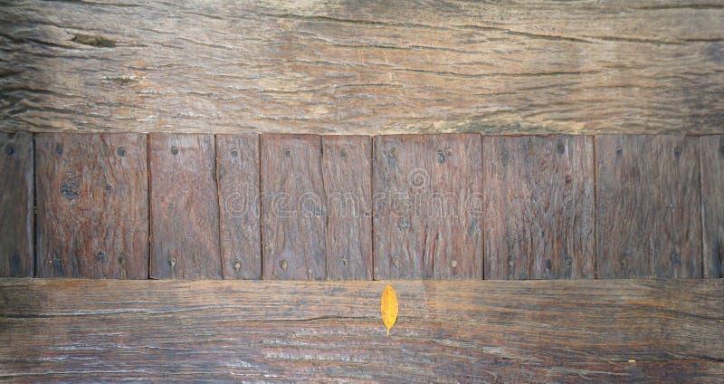 Коричневые листья помещены на нескольких старых деревянных плит которые прикалываны с ногтями стоковые изображения rf