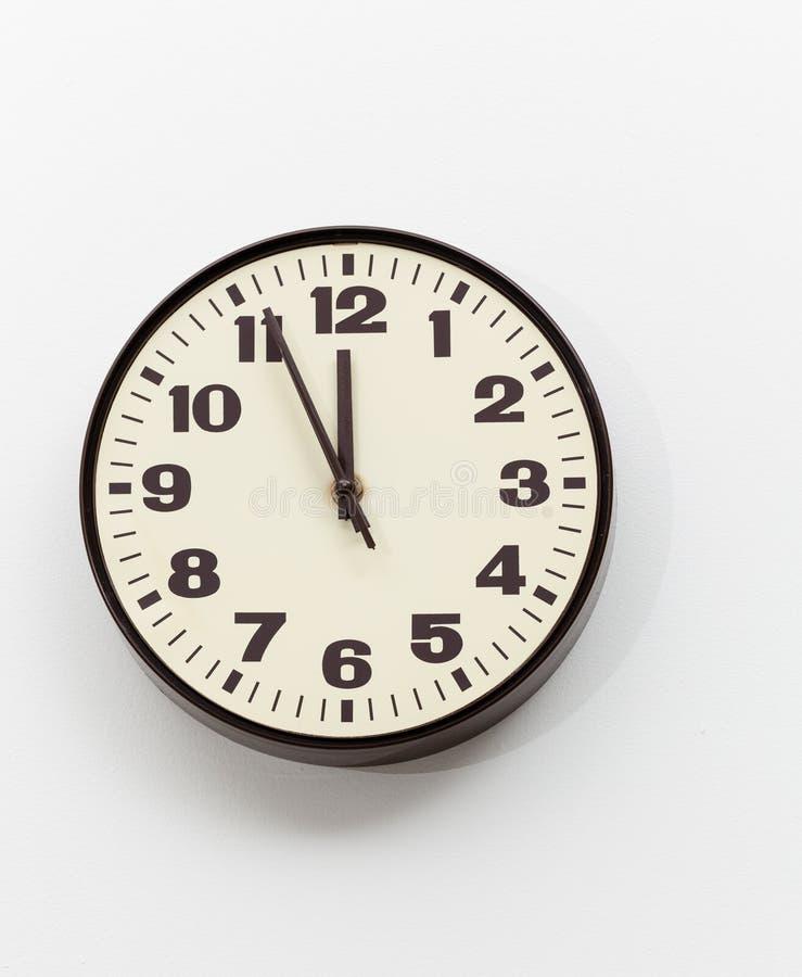 коричневые часы около белизны стены офиса полдня стоковое фото