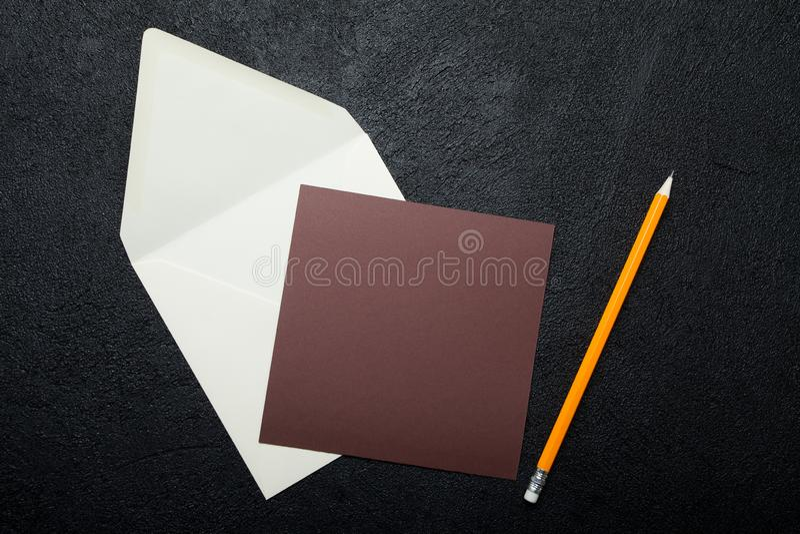Коричневый квадратный кусок бумаги и конверт на черной предпосылке стоковые фото