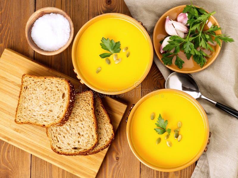 Коричневый шар 2 супа тыквы с семенами петрушки и тыквы на коричневой темной деревянной предпосылке, взгляд сверху стоковое фото rf