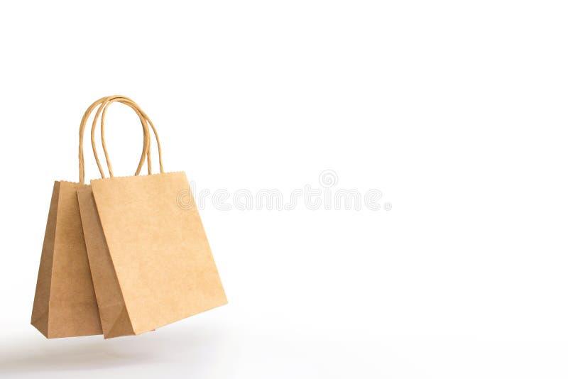 2 коричневых бумажных хозяйственной сумки с руками и тень изолированная на белой предпосылке стоковые фото