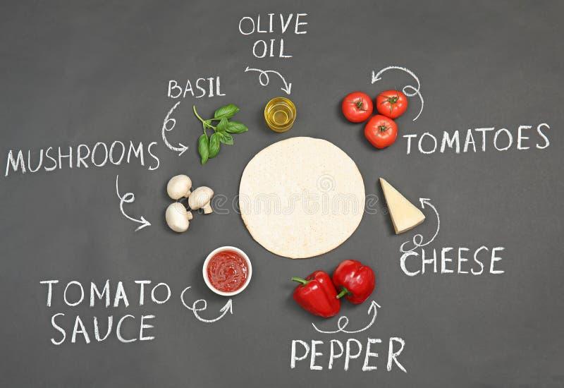 Корка пиццы, ингредиенты и продукта написанного имена мелом на темной предпосылке стоковая фотография rf