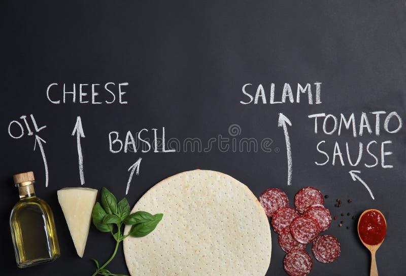 Корка пиццы, ингредиенты и продукта написанного имена мелом на черной предпосылке стоковая фотография