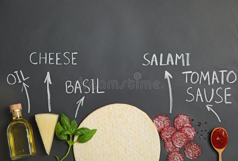 Корка пиццы, ингредиенты и продукта написанного имена мелом на черной предпосылке стоковое фото