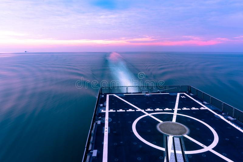 Кормка военного корабля и ламинарная подача воды созданной своим стимулируют с влиянием нерезкости движения перед заходом солнца стоковое фото