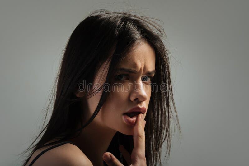 Кормовая молодая дама касаясь ее губам стоковая фотография