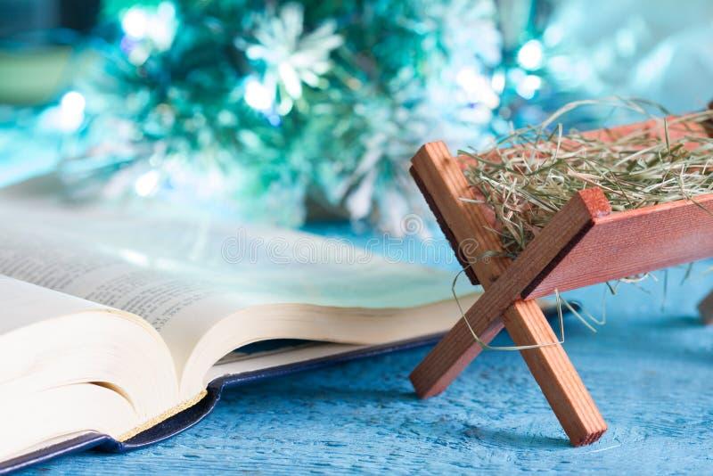 Кормушка библии и родная сцена резюмируют концепцию предпосылки рождества стоковые фото