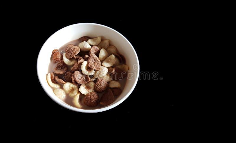 Корнфлексы ванили и шоколада окунули в шоколадном молоке в белом шаре в черной предпосылке стоковые изображения rf