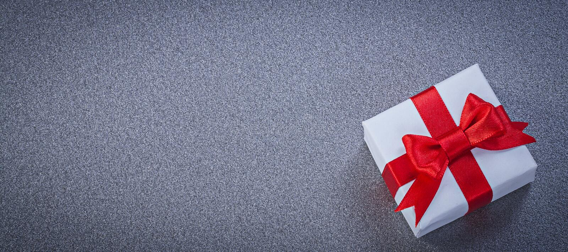 Коробка белизны присутствующая с красным цветом связала смычок на сером поверхностном космосе h экземпляра стоковые фотографии rf