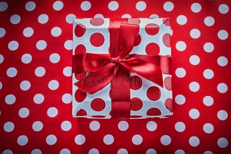 Коробка белизны присутствующая с связанной лентой на знаменитости ткани полька-точки красной стоковая фотография rf