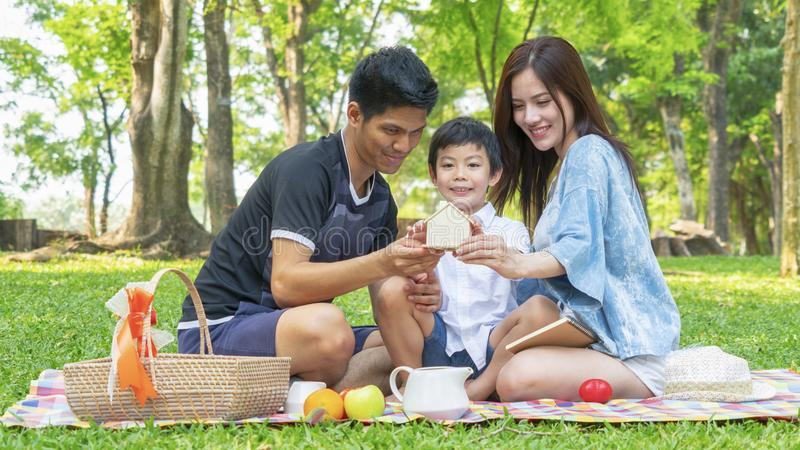 Коробка дома сбережений денег владением мальчика с матерью и отцом в парке Счастливая концепция пикника семьи стоковые изображения