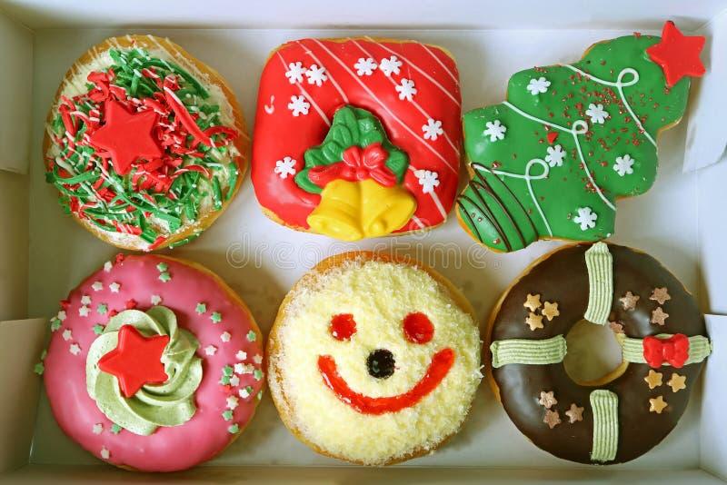 Коробка заполненная с красочным рождеством и праздничными украшенными помадками донутов стоковое изображение