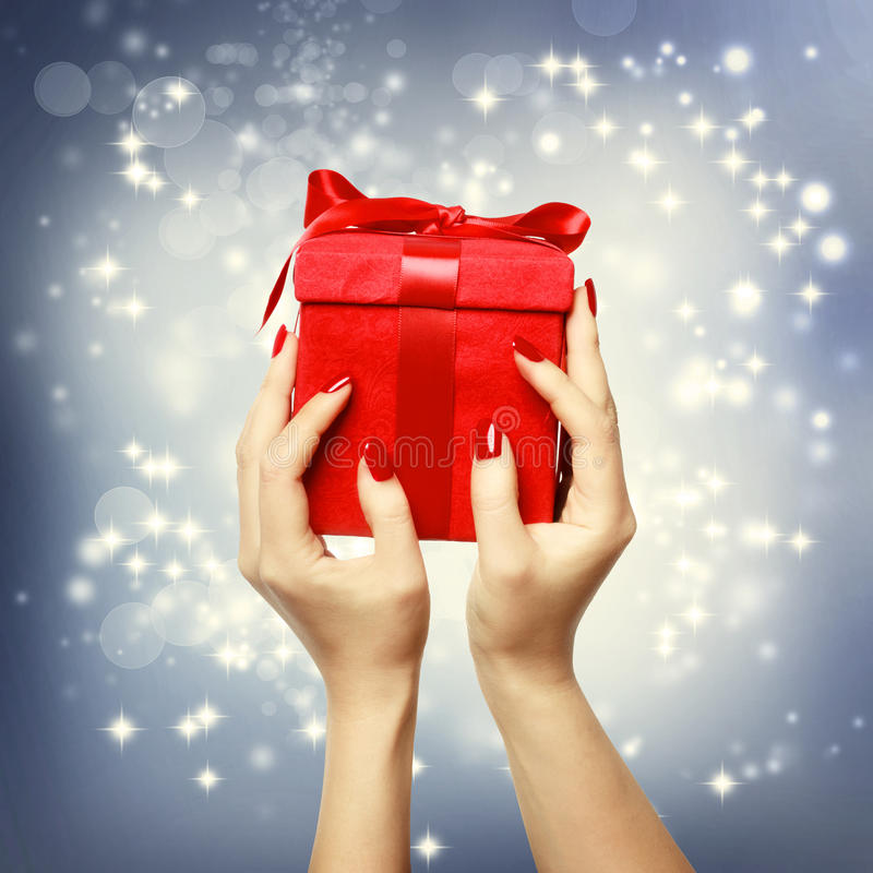 Коробка красного цвета присутствующая на рождестве на shinning предпосылке стоковые изображения