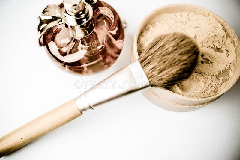 Коробка красоты, порошок с коричневой щеткой от ворсины для макияжа, розовые духи и серьги на предпосылке Плоское положение Взгля стоковые фото