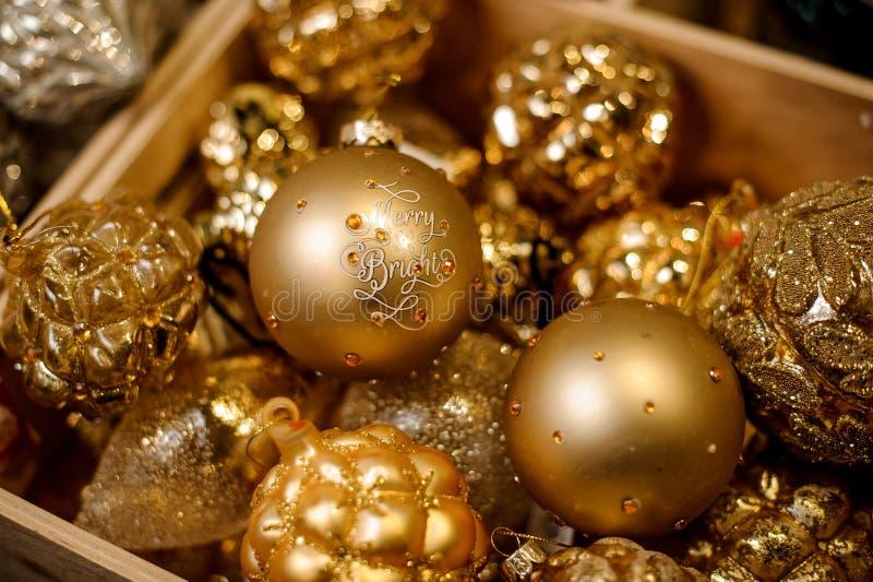 Коробка много блестящих золотых шариков игрушки различных форм стоковое изображение