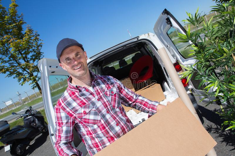 Коробка нося пакета картона работника доставляющего покупки на дом в передней поставке стоковое изображение rf
