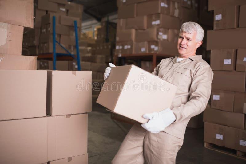 Коробка нося работника в складе стоковая фотография rf