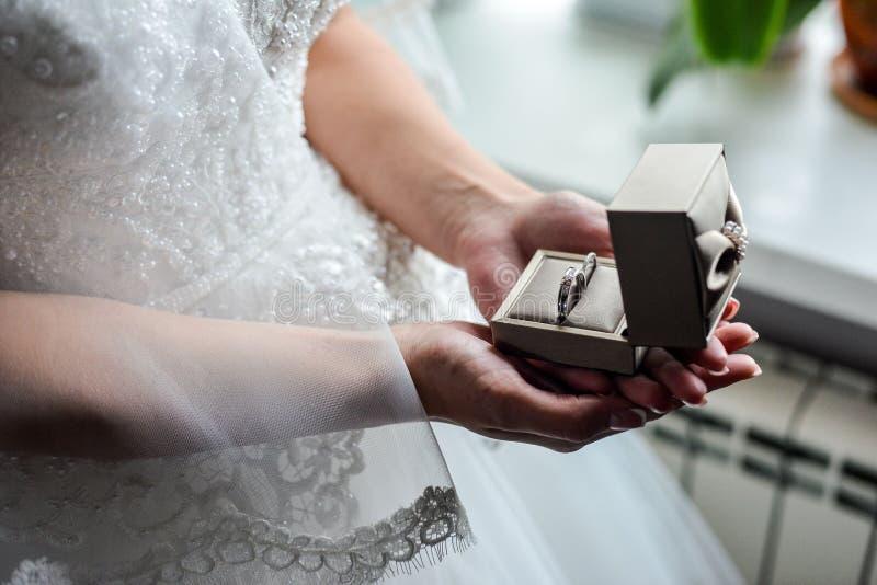 Коробка обручального кольца в руках невесты Крупный план ладоней женщины держа украшения стоковое изображение