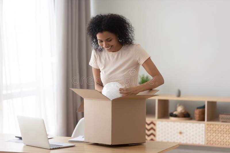 Коробка пакета счастливого удовлетворенного черного клиента девушки открытая дома стоковые фотографии rf