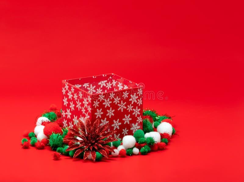 Коробка подарка на рождество окруженная пушистыми pompoms стоковые фотографии rf