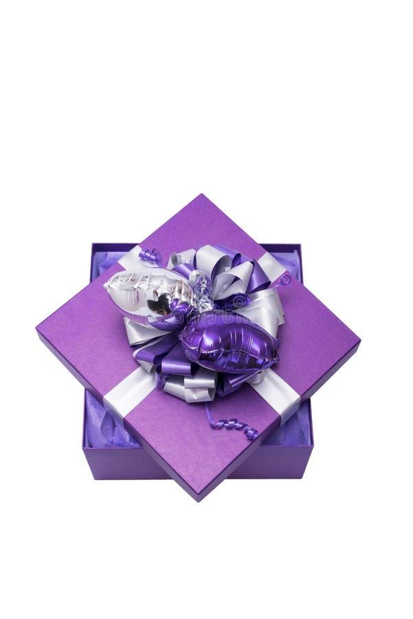 Коробка подарка фиолетовая с серебряными лентой и сердцем сформировала воздушный шар, iso стоковое фото