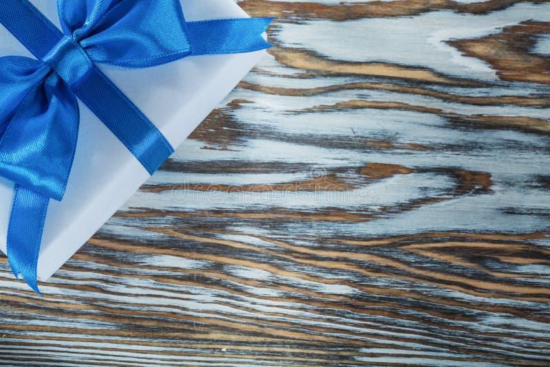 Коробка сини присутствующая с связанным смычком на винтажной деревянной доске стоковые фото