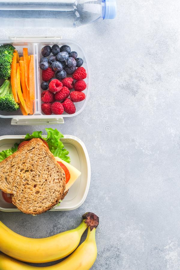 Коробка школьного обеда с миндалинами и плодоовощами воды овощей сандвича на серой таблице здоровой стоковое фото rf