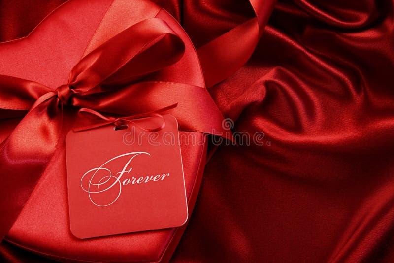Коробка шоколада крупного плана с карточкой подарка на сатинировке стоковые фотографии rf