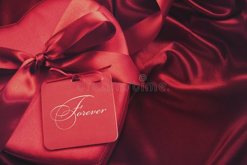 Коробка шоколада с карточкой подарка на сатинировке стоковая фотография