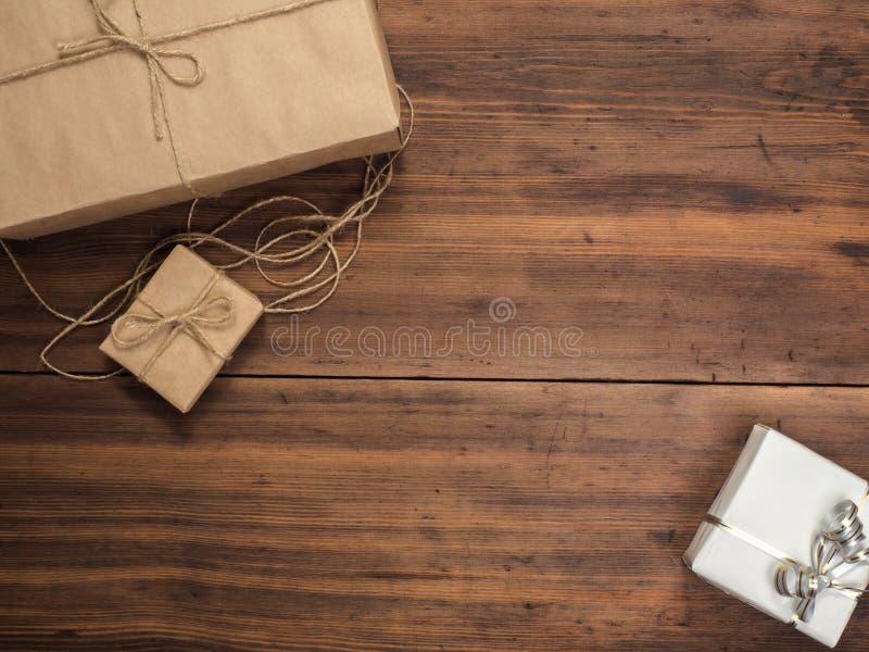 Коробки в бумаге ремесла, бумаге eco на деревянном столе Взгляд сверху Пакеты или подарки связанные с шпагатом Обернутая бумага Б стоковое изображение rf