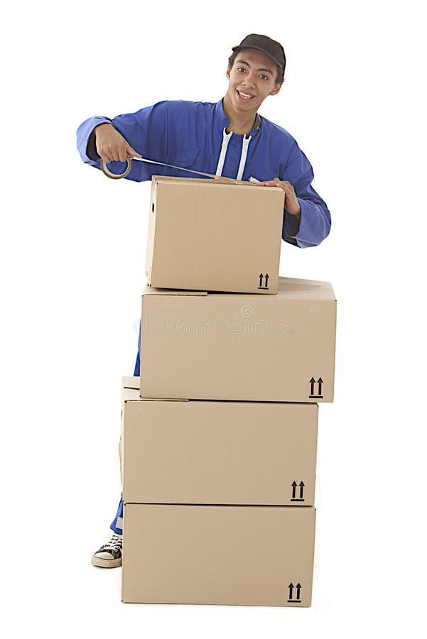 Коробки молодого профессионального мальчика курьера moving стоковое изображение