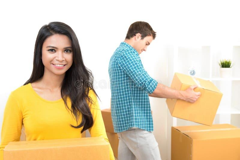 Коробки нося молодых пар двигая к новому дому стоковая фотография