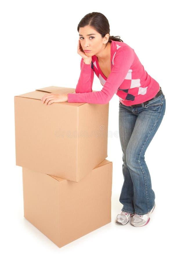 коробки полагаясь смотрящ утомленную женщину стоковое фото rf