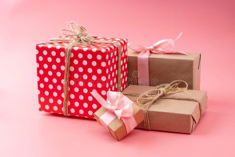 Коробки праздничного подарка упаковали в произведении бумаги и красных точек польки на розовой предпосылке Концепция красивых кар стоковая фотография rf