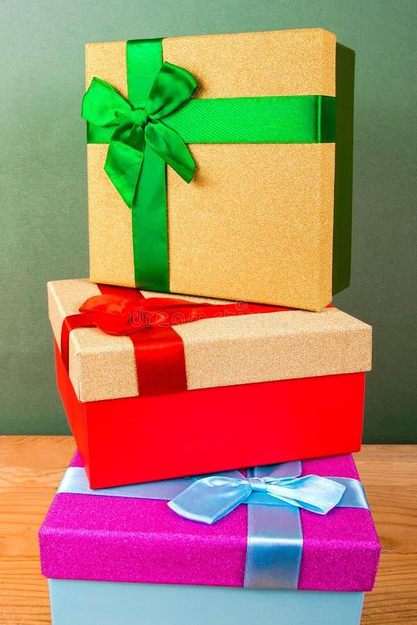 Коробки с смычками для подарков рождества друг к другу на зеленой предпосылке стоковое изображение rf