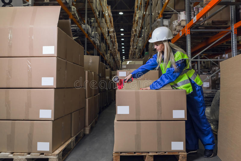 Коробки упаковки работника склада в storehouse стоковая фотография