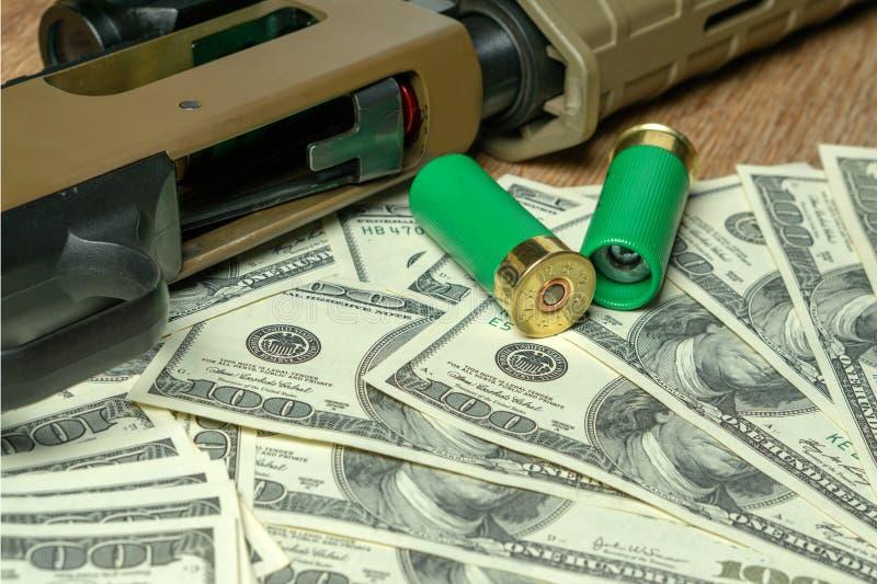 Корокоствольное оружие и патроны на долларах Преступление, продажа оружий Противозаконное звероловство стоковая фотография
