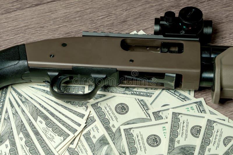 Корокоствольное оружие на долларах Концепция для преступления, глобальной торговли оружия, продажи оружий Противозаконное звероло стоковые изображения
