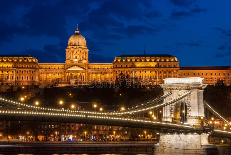 Королевский дворец или замок Буда и цепной мост после захода солнца в Будапеште в Венгрии стоковые фотографии rf