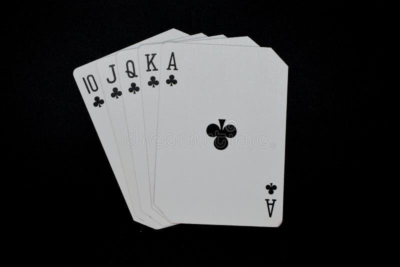 Королевский приток клубов в игре карточек казино покера подлинной на черной предпосылке стоковое фото