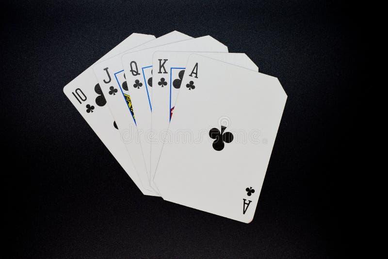Королевский приток клубов в игре карточек казино покера подлинной на черной предпосылке стоковые фото
