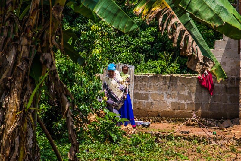 КОРОЛЕВСТВО BABUNGO - КАМЕРУН/01 19 2015: Африканская мать нося ее младенца на ей назад стоковые фотографии rf