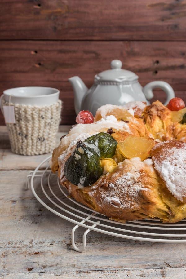 Король Испечь с гайками - Bolo Rei традиционный торт Xmas с изюминками гайкой и замороженностью плодов на деревянном столе стоковая фотография