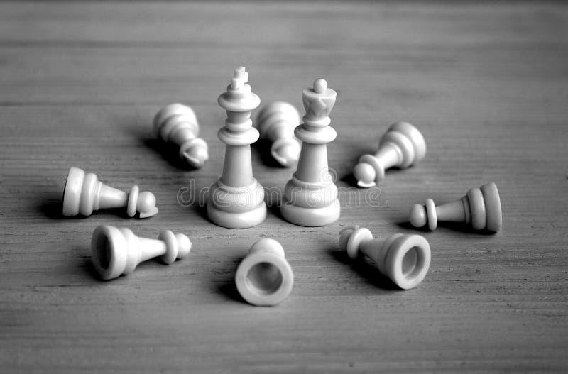 Король шахматной фигуры и стойка и пешки ферзя лежат на их ногах стоковая фотография rf