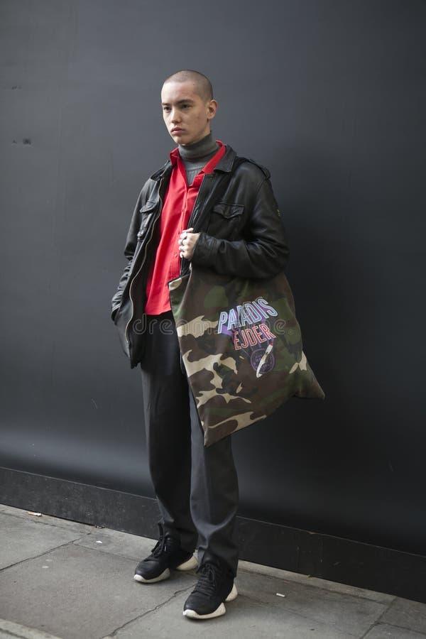 коротк-подрезанный серьезный молодой человек одел в спортивном стиле представляя во время недели моды Лондона стоковое изображение