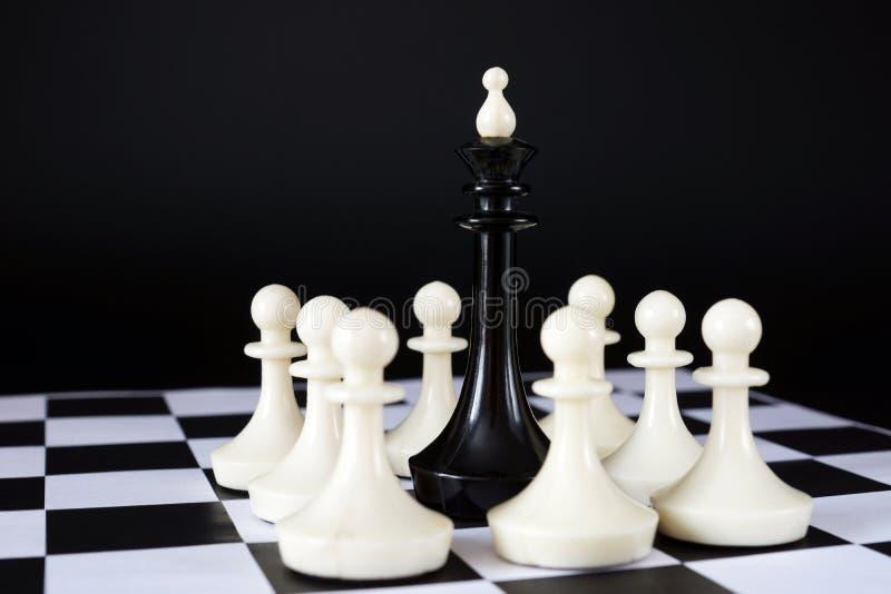 Король шахмат окруженный враждебными пешками Поражение и потеря стоковое изображение rf