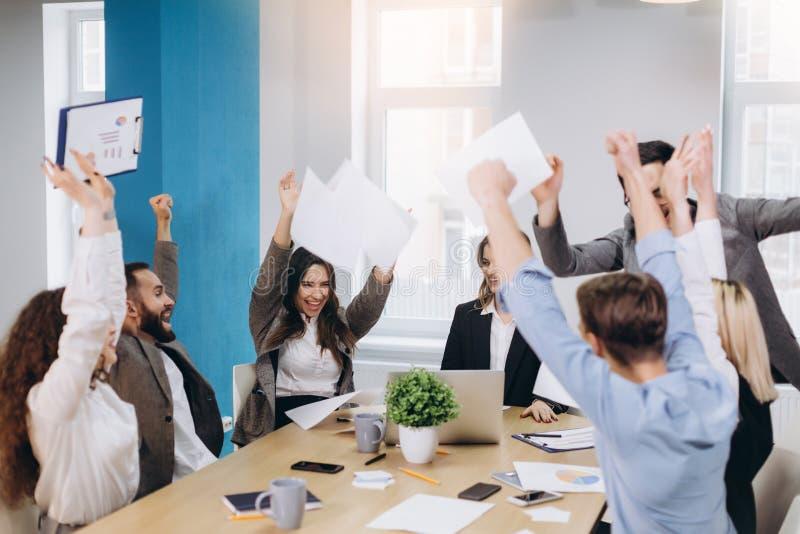 Многонациональная разнообразная счастливая команда празднует бумагу хода успеха проекта вверх совместно Корпоративная община, гра стоковые фотографии rf