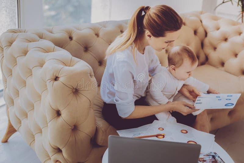 Корпоративное удаленное чувство работника принималось за новый проект пока нянчащ ее ребенка стоковое изображение rf